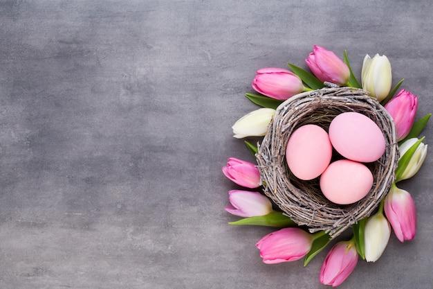 분홍색 계란 핑크 튤립 회색 배경에 둥지. 부활절 인사 카드.