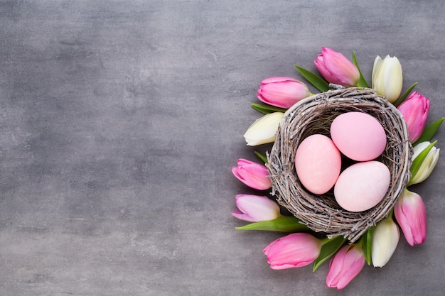 Розовый тюльпан с розовыми яйцами гнездится на сером фоне. открытка с пасхой.