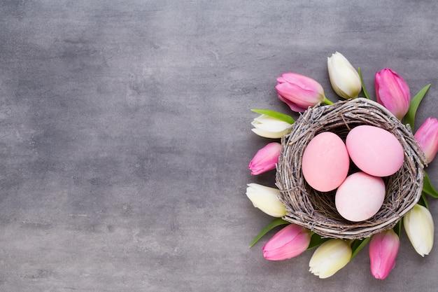 분홍색 계란 핑크 튤립 회색에 둥지. 부활절 인사 카드.
