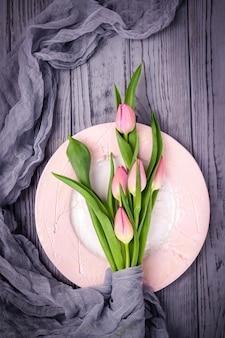 ピンクのチューリップと灰色の木製の壁のプレート