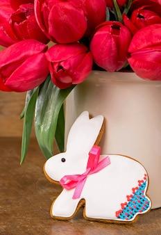 Розовые тюльпаны и печенье пасхального кролика на деревянных фоне.