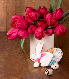 핑크 튤립과 나무 표면에 부활절 토끼 쿠키. 봄 또는 부활절 개념