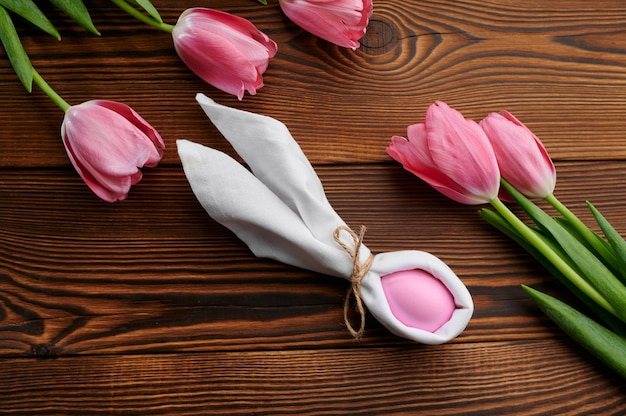 ピンクのチューリップと木製のテーブルのイースターエッグ。春の花が咲き、パスカルフード、休日のお祝いのための新鮮な花の装飾