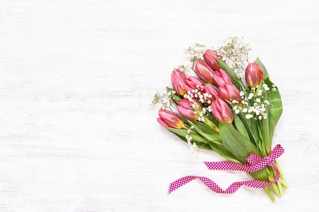 Букет розовых тюльпанов и гипсофилы, украшенный лентой на белом столе. копировать пространство, вид сверху