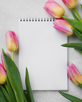 Pink tulips beside notebook