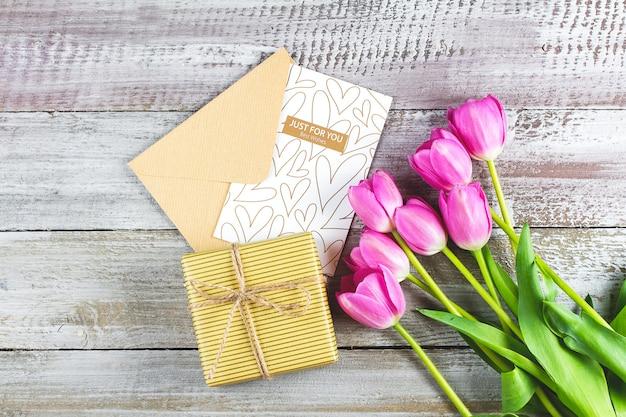 ピンクのチューリップの花束、グリーティングカード、木製のテーブルのギフトボックス。母の日やバレンタインデーのコンセプト。トップビュー、フラットレイアウト