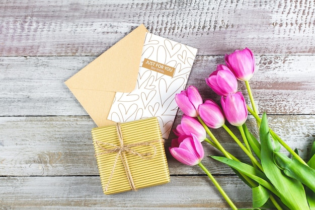 Pink tulips bouquet, greeting card and gift box on wooden table. mother's day or valentine's day concept. top view, flat lay