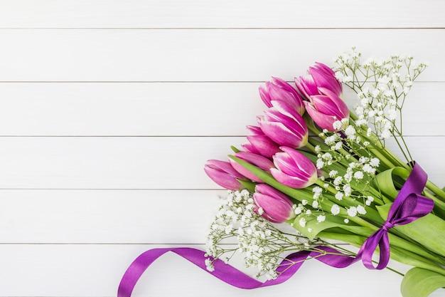 白い木製の背景にピンクのチューリップの花束。コピースペース、上面図。休日の背景