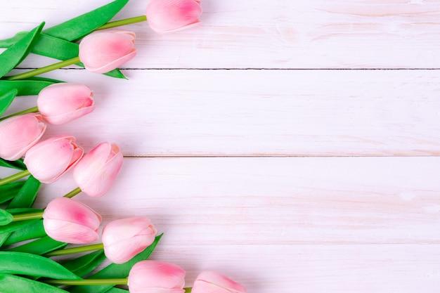 白い木製の表面にピンクのチューリップの花束
