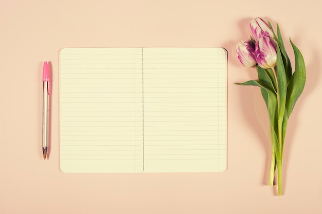 Pink tulips bouquet and open notebook