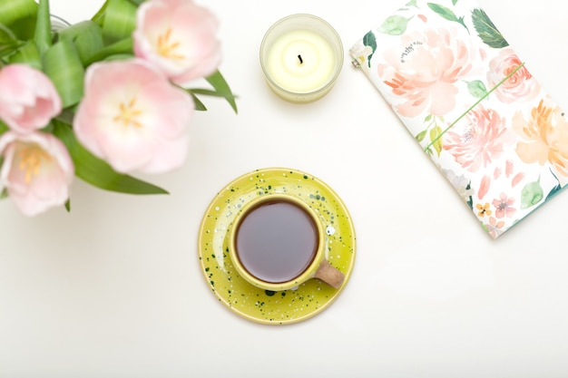 Pink tulips, chocolate, coffee cup, candle on white