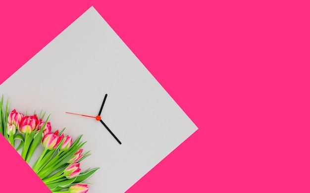 Pink tulips and clock hands on a gray and pink color block background copy space