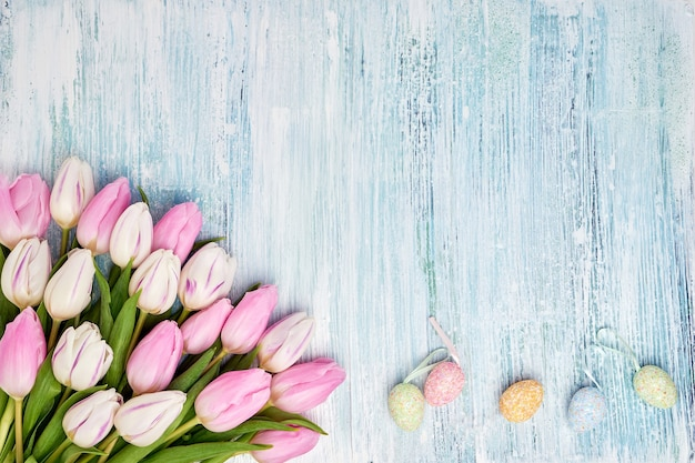 Pink tulips and decorative easter eggs on blue wall. top view, copy space. holiday wall.