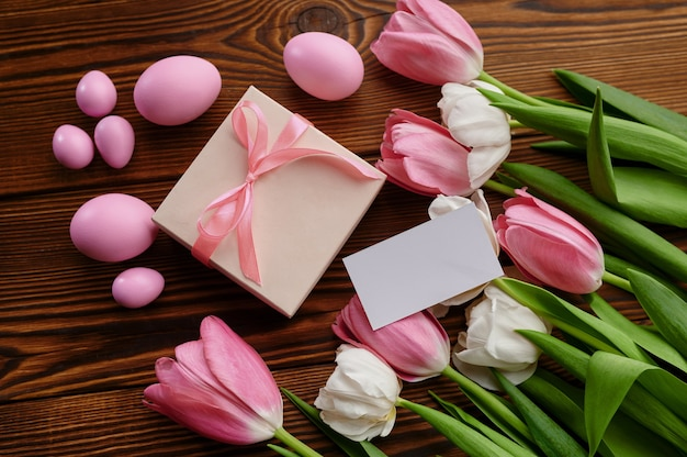 ピンクのチューリップ、イースターエッグ、木製テーブルのギフトボックス。春の花が咲き、パスカル料理、新鮮な花の装飾、休日のお祝いのシンボル