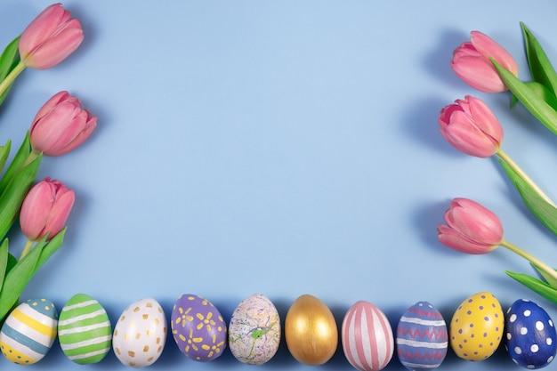 ピンクのチューリップの花とピンクの背景にカラフルな卵。ハッピーイースターのカード。春を待っています。グリーティングカード。こんにちは春とイースターのコンセプト。新鮮なチューリップ。フラットレイ、上面図、コピースペース