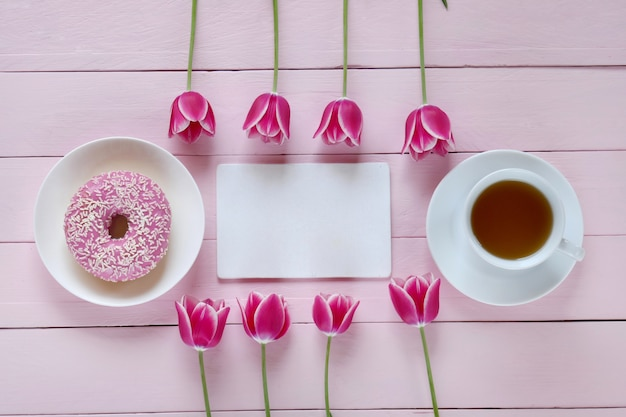 Pink tulips flowers, blank notebook, cup of tea and pink donut on a pink wooden background