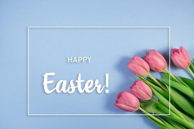 青い背景にピンクのチューリップの花。ハッピーイースターのカード。春を待っています。グリーティングカード。こんにちは春とイースターのコンセプト。フラットレイ、上面図、テキスト用のコピースペース