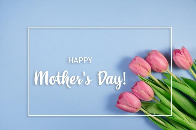 Розовые тюльпаны цветы на синем фоне. открытка на день матери, 8 марта. цветочная композиция с красивыми свежими тюльпанами. открытка ко дню матери. плоская планировка, вид сверху, длинный широкий баннер. копировать пространство