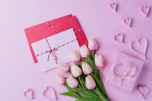Pink tulips, gift box with heart and red pink letter cover on pink background.