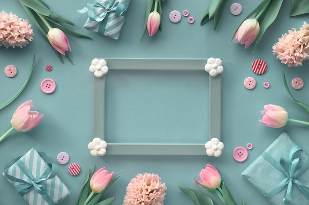 Pink tulips, hyacinth and spring decorations arond wooden frame with  text space