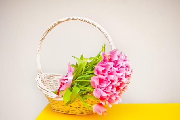 黄色のテーブルの上の白いバスケットにピンクのチューリップ