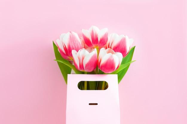 Розовые тюльпаны в подарочной коробке на розовом, плоская планировка
