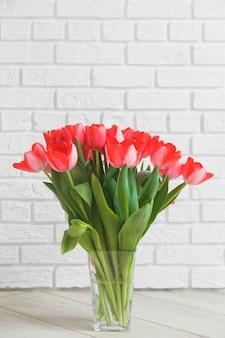 背景の白いレンガの壁にガラスの花瓶のピンクのチューリップ