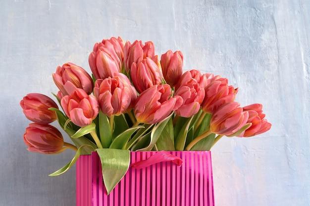 Розовые тюльпаны в розовом бумажном пакете с копией пространства, концепция праздника, поздравительная открытка