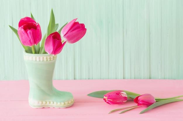 녹색 나무 바탕에 꽃병에 핑크 튤립