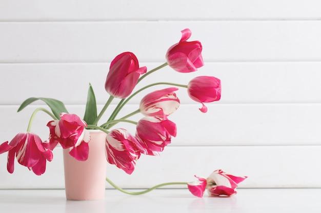 白い木製の背景の上に花瓶のピンクのチューリップ