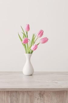 배경 흰 벽에 나무 테이블에 흰색 세라믹 꽃병에 핑크 튤립