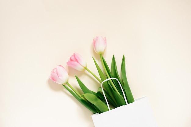 Розовые тюльпаны в белом картонном пакете на светло-желтом фоне