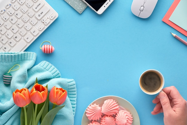 Pink tulips on mint colored cotton sweater, greeting cards and envelopes, keyboard, mobile phone, plate of marshmallow and cup of coffee.