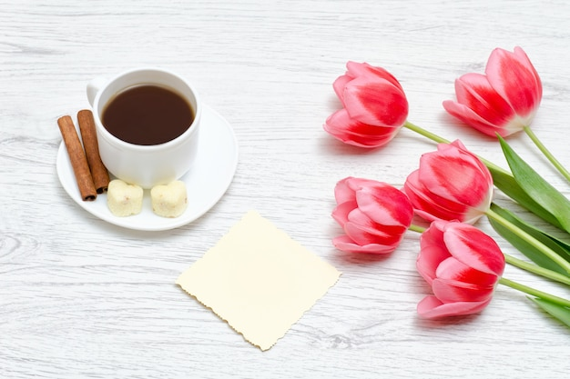 Pink tulips, mug of coffee and cinamon, light wooden background.