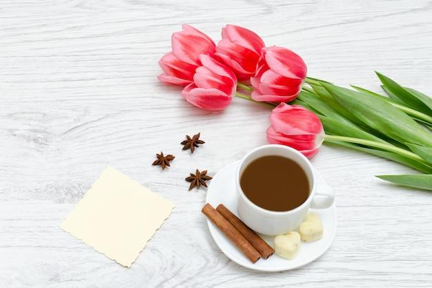 Pink tulips, mug of coffee and cinamon.