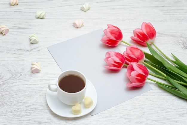 Pink tulips, mug of coffee and sheet of paper. light wooden background.