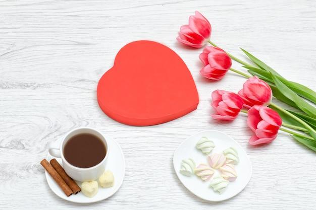 ピンクのチューリップ、マグカップのコーヒー、マシュマロ。赤いハート形のギフトボックス