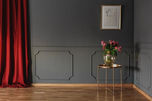 Розовые тюльпаны на золотом столе в углу роскошного интерьера с лепниной на темно-серых стенах и ярко-красными шторами. реальное фото