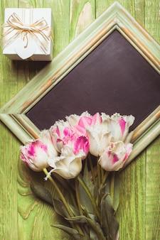 コピースペースのある緑の木製黒板にピンクのチューリップ。教師の日のコンセプト