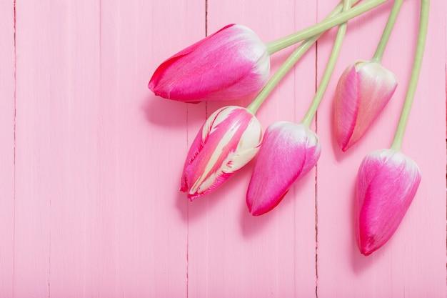 ピンクの木の表面にピンクのチューリップ