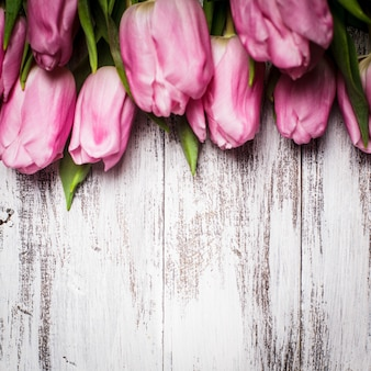 초라한 흰색 나무 테이블 위에 핑크 튤립