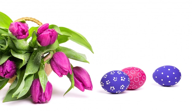 Pink tulips and painted easter eggs on white background