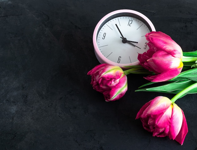 Pink tulips and pink alarm on the black chalkboard background