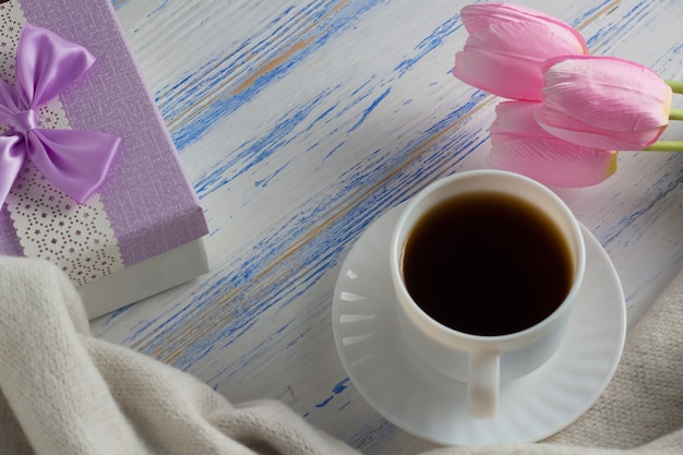 Pink tulips, scarf, coffee cup and gift box on a white wooden surface