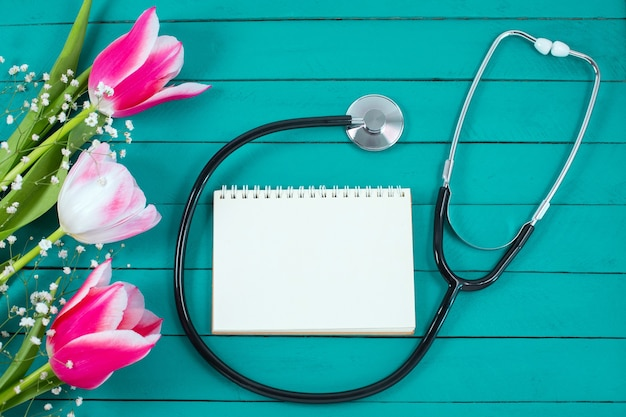 Pink tulips and stethoscope with spiral notepad with happy doctors day text on it.
