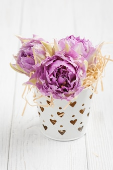 Pink tulips in tin bucket with heart-shaped holes