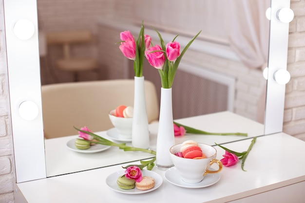 Pink tulips in vase, cup and macaroons on table in beauty salon
