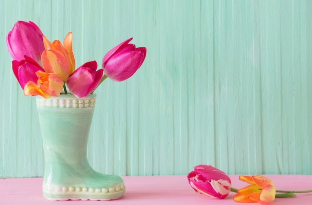 Pink tulips in vase on green wooden background