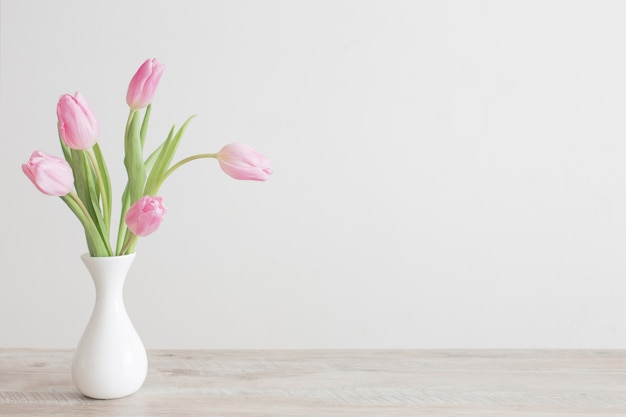 Pink tulips in white ceramic vase on wooden table on background white wall