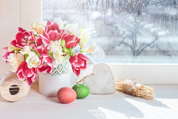 Pink tulips and white freesia flowers on the window board, easter decorations